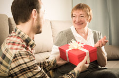 Son giving present to mother Royalty Free Stock Image