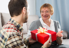 Son giving present to mother Stock Image