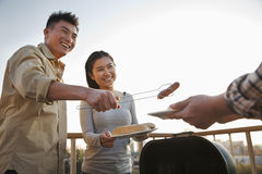 Son giving sausage to his father over the barbeque Stock Photography