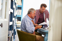 Son Giving Senior Parent Financial Advice In Home Office Stock Image