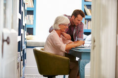 Son Giving Senior Parent Financial Advice In Home Office Stock Photography