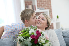 Son giving a surprise buquet to his mother. Young boy giving flowers to mommy for mother's day Royalty Free Stock Images