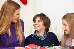 Son giving to his mother a gift for christmas. Happy family celebrating together christmas Stock Photography