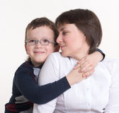 Son in glasses hugging her mother's shoulders. In studio Stock Photo
