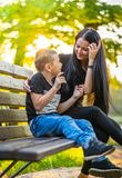 Son Glazing in His Mother`s Eyes on a Park Bench in Autum Colorf. Ul Background, Sun Shining over their Faces - Caption on Shirt `I am, It`s now or never, Iask stock images