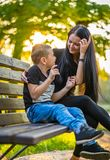 Son Glazing in His Mother`s Eyes on a Park Bench in Autum Colorful Background, Sun Shining over their Faces royalty free stock photo