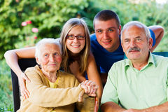 Son and Grandchildren Visiting Granny. Happy family visiting the grandmother in the garden of the nursing home Stock Photo