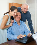 Son halping his perents with laptop. Manager helping to senior couple with laptop Royalty Free Stock Image