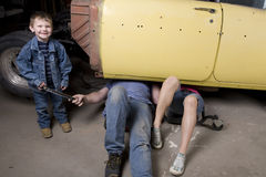 Son handing father a tool. A son handing his father a tool while he and his wife are under the car working stock image