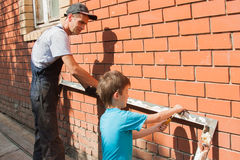 Son, helped a father. That cuts away old material from a frisket Royalty Free Stock Photos