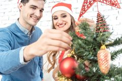 Son helping family decorating the Christmas tree royalty free stock photo