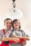 Son helping father changing a lightbulb. In a ceiling lamp Stock Images