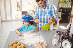 Son helping father in preparing food. High angle view of son helping father in preparing food at home Stock Photos