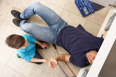 Son Helping Father To Mend Sink. In Kitchen stock photography