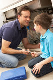 Son Helping Father To Mend Sink. In Kitchen stock photos