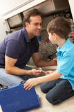 Son Helping Father To Mend Sink. In Kitchen royalty free stock images