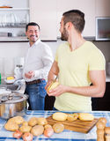 Son helping father to prepare. Adult son helping happy father to prepare vegetable stew at kitchen Royalty Free Stock Photos