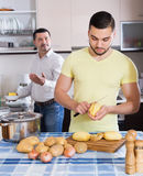 Son helping father to prepare. Adult serious son helping father to prepare vegetable stew at kitchen Stock Images