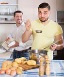 Son helping father to prepare. Adult son helping smiling father to prepare vegetable stew at kitchen Royalty Free Stock Images