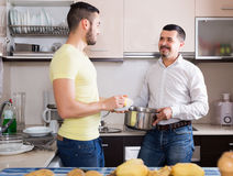 Son helping father to prepare. Adult son helping father to prepare vegetable stew at kitchen Stock Photo