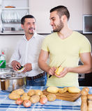Son helping father to prepare. Positive adult son helping father to prepare vegetable stew at kitchen Stock Images