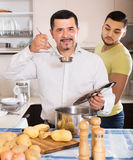 Son helping father to prepare. Son helping positive father to prepare vegetable stew at kitchen Royalty Free Stock Photography