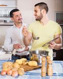 Son helping father to prepare. Positive young son helping father to prepare vegetable stew at kitchen Stock Photos