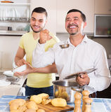 Son helping father to prepare. Smiling adult son helping happy father to prepare vegetable stew at kitchen Royalty Free Stock Photography