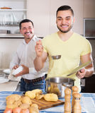 Son helping father to prepare. Smiling adult son helping father to prepare vegetable stew at kitchen Stock Photography