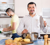 Son helping father to prepare. Son helping smiling father to prepare vegetable stew at kitchen Royalty Free Stock Image