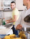Son helping father to prepare. Smiling young son helping father to prepare vegetable stew at kitchen Stock Images