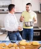 Son helping father to prepare. Young son helping father to prepare vegetable stew at kitchen Royalty Free Stock Photo