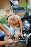 Son helping father to repair the bike . Stock Photos