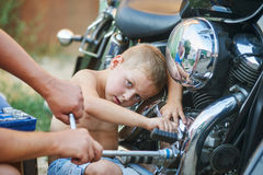 Son helping father to repair the bike . Stock Photo