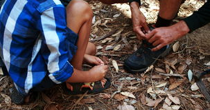 Son helping father to tie his shoe lace in the park. On a sunny day stock footage