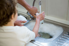 Son helping father in washing utensils. In the kitchen sink Royalty Free Stock Photos