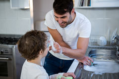 Son helping father in washing utensils. In the kitchen sink Stock Photo