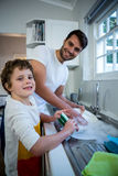 Son helping father in washing utensils. Portrait of son helping father in washing utensils in the kitchen sink Stock Photos