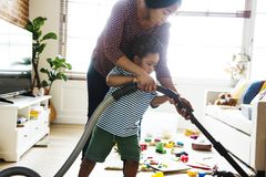 Son helping his mother clean the room Stock Photos
