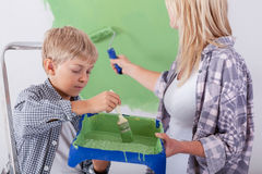 Son helping his mother painting a wall. Cute little son helping his mother painting a wall Royalty Free Stock Image
