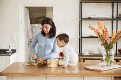 Son Helping Mother To Prepare Food On Kitchen Island Royalty Free Stock Images