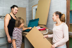 Son helping parents. To unpack boxes in new house Stock Images