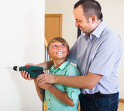Son helping proud father to drill wall Stock Image