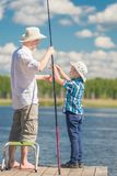 Son helps his father to fish. In the lake royalty free stock photo