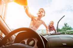Son helps his father to wash a car stock images