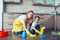 Son helps mom clean up in the kitchen. Parenting stock images