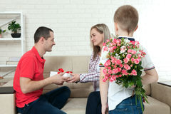 Son hiding bouquet to surprise mommy on mother`s day. Woman, man Royalty Free Stock Photo