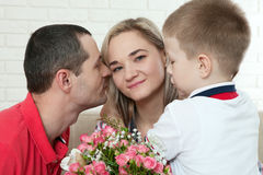 Son hiding bouquet to surprise mommy on mother`s day. Woman, man Stock Image