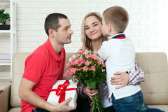 Son hiding bouquet to surprise mommy on mother`s day. Woman, man. Son hiding bouquet to surprise mommy on mother`s day. Woman, men child hugs and kisses Royalty Free Stock Photography