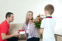 Son hiding bouquet to surprise mommy on mother`s day. Woman, man Stock Photos